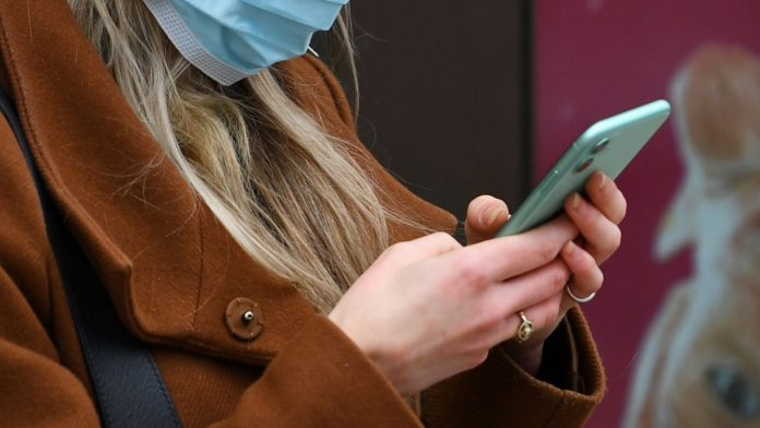 A woman looks at her phone whilst wearing a mask in London